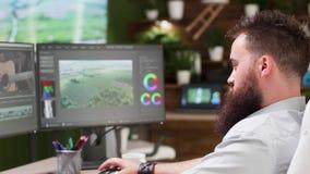 Tillbaka sikt av den stilfulla nöjda skaparen som arbetar på hans dator stock video