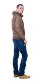 Tillbaka sikt av den stiliga mannen i den bruna vindtygsjackan som ser upp Arkivbild