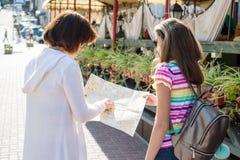 Tillbaka sikt av den tonåriga turisten för mamma som och för dotter ser på översikten Royaltyfri Foto