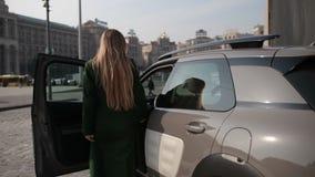 Tillbaka sikt av den trendiga kvinnan som får in i bilen lager videofilmer