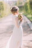 Tillbaka sikt av den unga blonda bruden i den vita klänningen som ser den utomhus- brud- buketten Arkivfoto