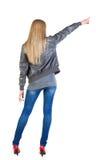 Tillbaka sikt av den unga blonda kvinnan som pekar på väggen Fotografering för Bildbyråer