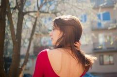 Tillbaka sikt av den unga brunettkvinnan med vinden som bl?ser h?r, sinnliga kanter och den r?da skjortan p? stads- bakgrund f?r  fotografering för bildbyråer