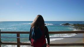 Tillbaka sikt av den unga kvinnan med ryggsäcken och halsduken som får närmare staketet på havstranden stock video