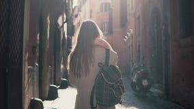 Tillbaka sikt av den unga kvinnan som går på stadsgatan i Europa på morgonen Flicka som undersöker den ensamma gamla staden och a royaltyfri foto