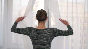 Tillbaka sikt av den unga kvinnan som upp till kommer fönstret som avtäcker gardiner och ser ut ur fönster Tycka om sikten utanfö stock video