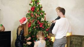 Tillbaka sikt av den unga lyckliga glade familjen av en iklädd Santa Claus för moder hatt, en fader och dekorera för två gulligt  arkivfilmer