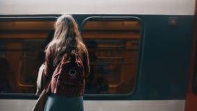 Tillbaka sikt av den unga studentkvinnan med ryggsäcken som nära står i tunnelbana nära det snabba ridningdrevet som väntar på en lager videofilmer