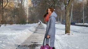 Tillbaka sikt av den unga vuxna flickan som går dra hennes stora violetta resväska under tidig vårtid på bakgrund för blå himmel lager videofilmer