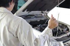 Tillbaka sikt av den yrkesmässiga unga mekanikermannen i enhetlig innehavskiftnyckel mot bilen i öppen huv på reparationsgaraget Fotografering för Bildbyråer