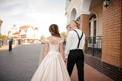Tillbaka sikt av det unga och lyckliga le gifta paret som går i stad arkivfoto