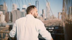 Tillbaka sikt av det vuxna Caucasian mananseendet vid stänger för Brooklyn bro som tycker om fantastisk cityscapesikt och bort gå arkivfilmer