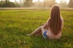 Tillbaka sikt av en attraktiv ung kvinna med lång sitti för mörkt hår royaltyfri bild