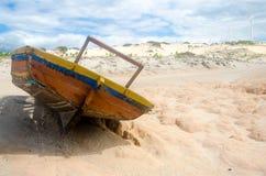 Tillbaka sikt av en bruten kanot över sanden Royaltyfri Bild