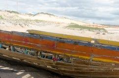 Tillbaka sikt av en bruten kanot över sanden Arkivfoto