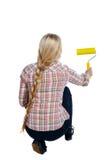Tillbaka sikt av en flicka som målar målarfärgrullen Folksamling för bakre sikt Royaltyfri Foto