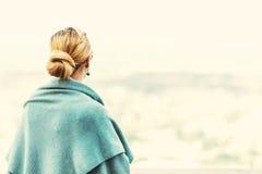 Tillbaka sikt av en kvinna med bundet blont hår Arkivfoto