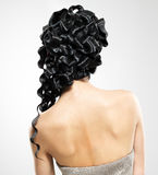 Tillbaka sikt av en kvinna med den lockiga frisyren för fashoin Arkivfoto
