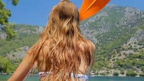 Tillbaka sikt av en kvinna som kayaking i havet lager videofilmer