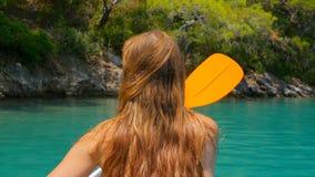 Tillbaka sikt av en kvinna som kayaking i havet stock video