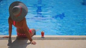 Tillbaka sikt av en kvinna som kopplar av i simbassäng lager videofilmer