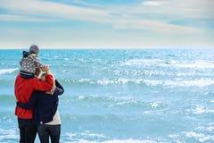 Tillbaka sikt av en lycklig familj på den tropiska stranden på sommarsemester Royaltyfri Bild