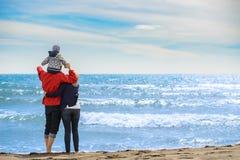 Tillbaka sikt av en lycklig familj på den tropiska stranden på sommarsemester Arkivbild