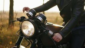 Tillbaka sikt av en man i hjälm- och läderomslaget som upp till kommer hans cykel och starten motorn, medan stå på lager videofilmer