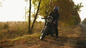 Tillbaka sikt av en man i hjälm- och läderomslaget som upp till kommer hans cykel och starten motorn, medan stå på stock video