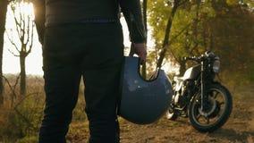 Tillbaka sikt av en man i svart jeans och läderomslaget som rymmer hans hjälm i hans hand, medan stå med hans kalla cykel på a stock video