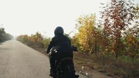 Tillbaka sikt av en man i svart motorcykel för hjälm- och läderomslagsridning på en asfaltväg på solig dag i höst Träd lager videofilmer