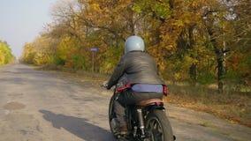 Tillbaka sikt av en man motorcykel för ridning i för det gråa hjälm- och läderomslaget och för plädskjortan på en asfaltväg på so stock video