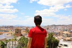 Tillbaka sikt av en man som ser Malaga cityscape, Andalusia, Spanien royaltyfri fotografi