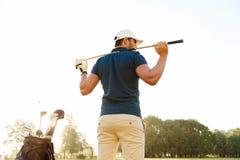 Tillbaka sikt av en manlig golfspelare på kursen med en klubbasäck Arkivfoto
