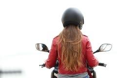 Tillbaka sikt av en motorbiker på en motorcykel på vit arkivbild
