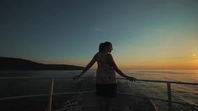 Tillbaka sikt av en nätt ung brunhårig flicka som poserar på däck av ett skepp Hennes händer på ledstängerna Obetydlig vind är lager videofilmer