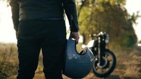 Tillbaka sikt av en oigenkännlig man i svart jeans och läderomslaget som rymmer hans hjälm i hans hand, medan stå förbi stock video