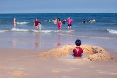 Tillbaka sikt av en pojke i rött t-kort sammanträde på stranden royaltyfria foton