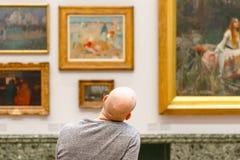 Tillbaka sikt av en skallig man som beundrar målningar som visas på Tate Bri royaltyfria bilder