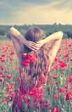 Tillbaka sikt av en ung kvinna med långt blont hår i en röd klänning som rymmer en bukett av blommor i ett vallmofält Arkivbild
