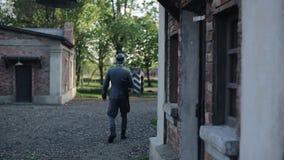 Tillbaka sikt av en ung man i en tysk likformig som WW2 går yttersidan Historiska byggnader för röd tegelsten på bakgrunden arkivfilmer