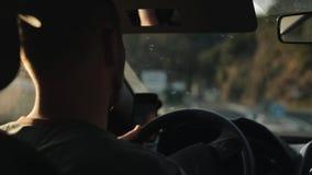 Tillbaka sikt av en ung manlig chaufför med skägget som vänder styrninghjulet Suddig bild av yttersidan arkivfilmer