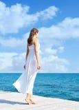 Tillbaka sikt av ett anseende för ung kvinna på en pir Havs- och himmelbaksida Arkivbilder