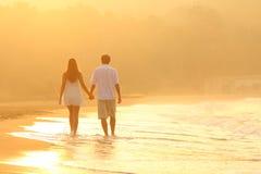 Tillbaka sikt av ett par på solnedgången som går på stranden arkivbild