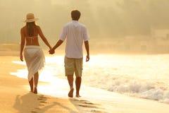 Tillbaka sikt av ett par som går på stranden på soluppgång arkivbild