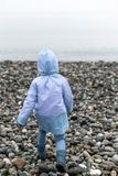 Tillbaka sikt av ett rinnande barn till havet i en regnrock och gummistöveler Selektivt fokusera royaltyfri foto