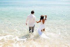 Tillbaka sikt av ett ungt rättvist gift par två att skriva in i kläder i vatten, sommartid, ferie i Grekland br?llopsresa royaltyfria bilder