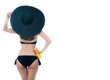 Tillbaka sikt av flickan i svart bikini och stor svart hatt Arkivbilder