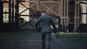 Tillbaka sikt av gå för soldat som är rakt rymma ett gevär och en hjälm i hans händer WWII-reenactment arkivfilmer