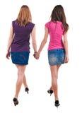 Tillbaka sikt av gå för två ungt kvinnor Arkivfoton